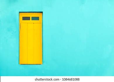 Blue tropical facade with yellow door. Colourful colonial Caribbean tropical style cyan facade with yellow closed window in a bright cyan wall house background. Simple house front negative space.