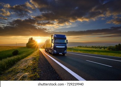 Blue truck driving on the asphalt road in rural landscape at sunset between dark clouds
