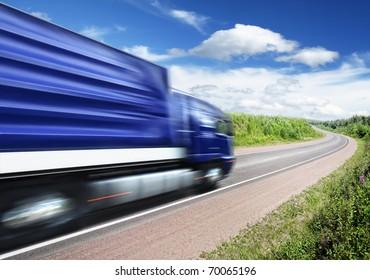 blue truck speeding on country highway, motion blur