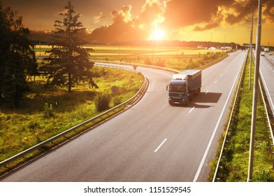 Blue truck with the trailer on the countryside road with fields and green trees against night sky with sunset