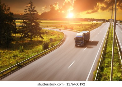 Blue truck with the trailer on the countryside road in motion with fields and green trees against night sky with sunset