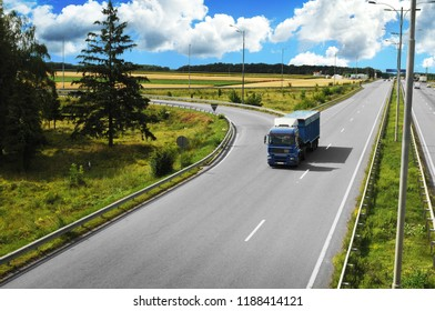 Blue truck with the trailer on the countryside road with fields and green trees against blue sky with clouds
