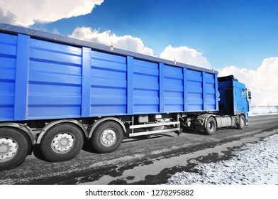 Blue truck and a trailer on the winter countryside road with snow against blue sky with clouds