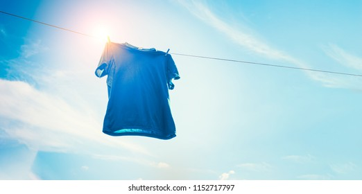 Blue t-shirt on clothes line against sun and blue sky with clouds.
