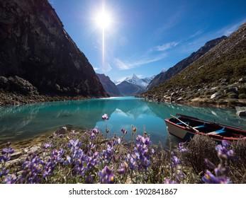 Blue turquoise alpine mountain lake Laguna Paron boat flower reflection in Caraz Huaraz Ancash Cordillera Blanca Peru