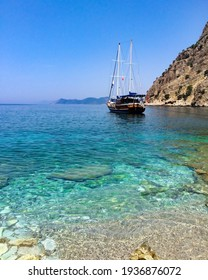 Blue and turquoise crystal clear waters of a rocky beach in south Turkey with a tourist leisure boat in the background
