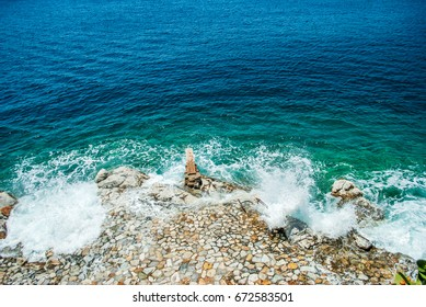 Blue and turquoise sea and sharp rocks that surrounds it