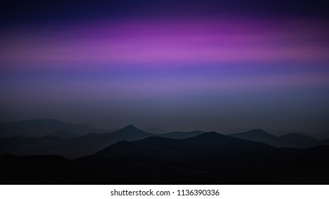 blue twilight over wavy mountain silhouettes