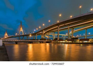 Blue twilight twin suspension bridge water front, cityscape background