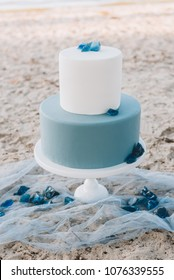 Blue two-tiered wedding cake on a sandy beach, decorated with blue stones.