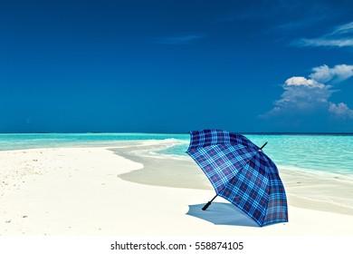 Blue umbrella is on a coral sandy beach, Maldives, The Indian Ocean