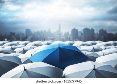 Blue umbrella on top of other gray umbrellas on city background. Business and safety concept