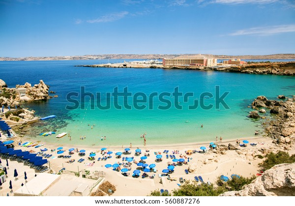 Blue umbrella on tropical beach with white sand, turquoise sea water and blue sky at deserted island in Malta, Paradise bay.