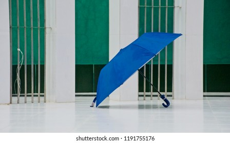 A blue umbrella on a white tiles surface unique blurry photo