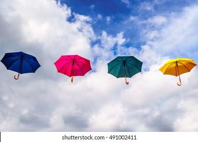Blue Umbrella, Red Umbrella, Green Umbrella and Yellow Umbrella floating in the Air under Blue and Cloudy Sky