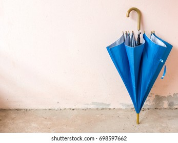The blue umbrella rests on the old wall