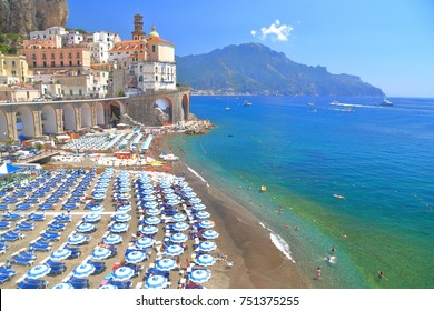 Blue umbrellas aligned on a beach in Atrani, Amalfi coast, Italy