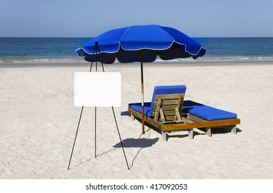 Blue umbrellas and beach chairs with a blank whiteboard at the sea.