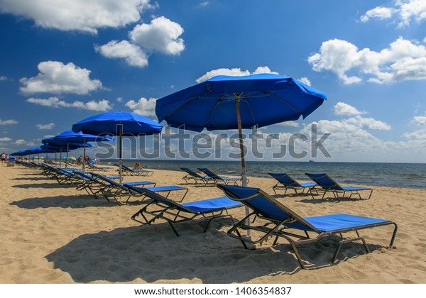 blue-umbrellas-tanning-chairs-installed-