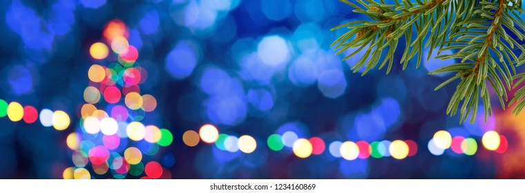 Blue unfocused background with colored christmas tree