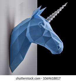 Blue unicorn's head hanging on the contrast white and black shadowed wall.Horse has intresting geometrical shape and straight lines. Original decoration for modern design.