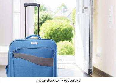 Blue vacation suitcase by opened front door.