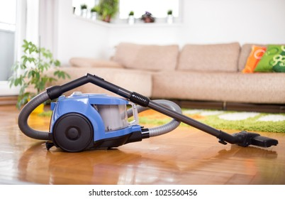 Blue vacuum cleaner standing on parquet floor in front of sofa in living room