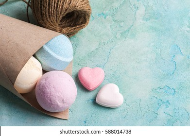 Blue, vanilla and strawberry bath bombs in the cone on turquoise concrete background
