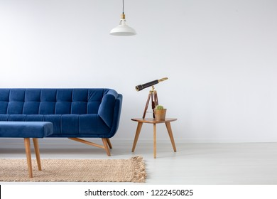 Blue velvet couch next to wooden coffee table with cactus in pot and telescope, real photo with copy space on the empty white wall and natural carpet on the floor