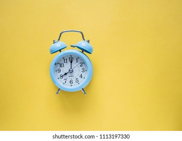 Blue vintage alarm clock on yellow color background