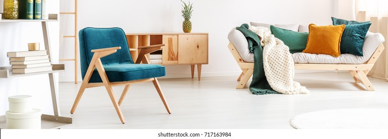 Blue vintage chair in bright room with orange and green pillow on sofa and pineapple on cupboard