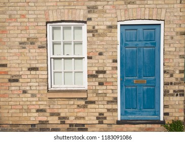 Blue vintage front door on a restored brick wall of a Georgian house residential building with white wooden sash window