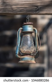 Blue vintage kerosene lantern hanging in front of weathered wooden clap boards