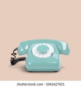Blue vintage telephone on pastel color