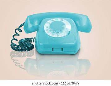Blue vintage telephone on pink background