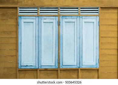 blue vintage wooden window on yellow wood wall