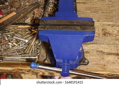 Blue vise on a wooden table. Bench tools. Vice.
