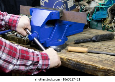 Blue vise on a wooden table. Bench tools. Vice. Men's hands hold a vise. A locksmith vise