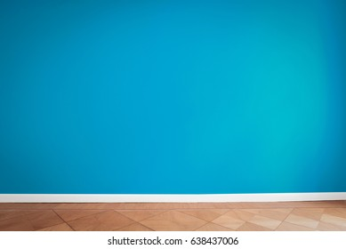 blue wall background in empty room , parquet floor