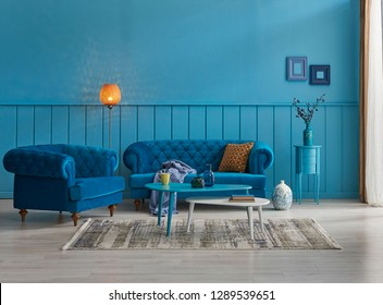 Blue wall and background room, decorative sofa and middle table, armchair and pillow detail, lamp and frame decoration with carpet decor.