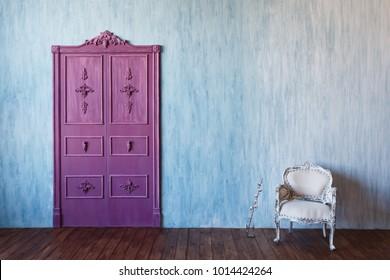 Blue wall cement, pink purple double-leaf door, loft furniture armchair. Copyspace