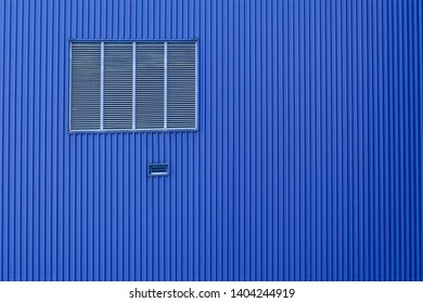 Blue wall made of rolled iron sheet and ventilation window.