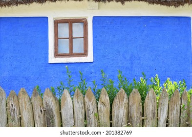 Blue wall of an old house with single window and wooden fence