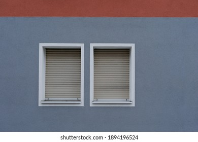Blue wall with red stripe, two windows with  aluminum shutter, jalousie rolled up symbol for lockdown, no person
