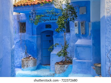 Blue wall and staircase decorated with colourful flowerpots.