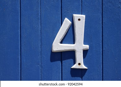 A blue wall with the street number four on it