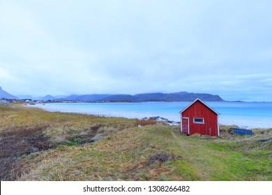 Blue water at beach Rambergstranda with typical red fisher hut in Ramberg, Norway