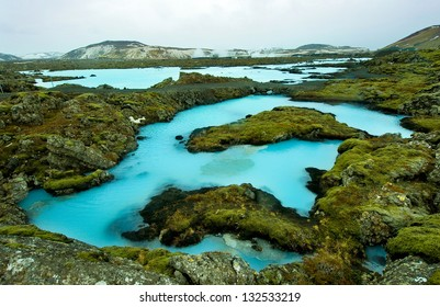 The blue water between the lava stones covered with moss just outside the Blue Lagoon resort of Iceland