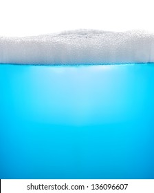 Blue water with foam or soap, isolated on white