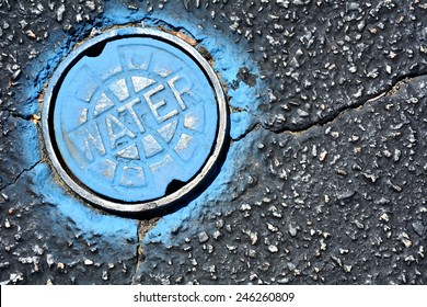 Blue water main on asphalt